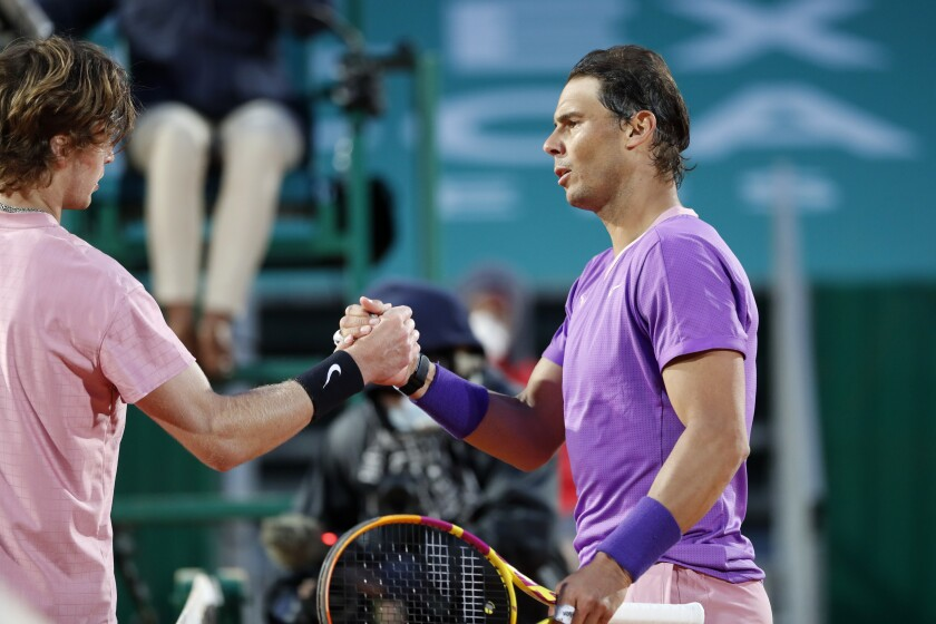 Rafael Nadal of Spain shakes hands with Andrey Rublev of Russia, left, at the end of their quarterfinal match of the Monte Carlo Tennis Masters tournament in Monaco, Friday, April 16, 2021. Rublev defeated Nadal 6-2/4-6/6-2. (AP Photo/Jean-Francois Badias)