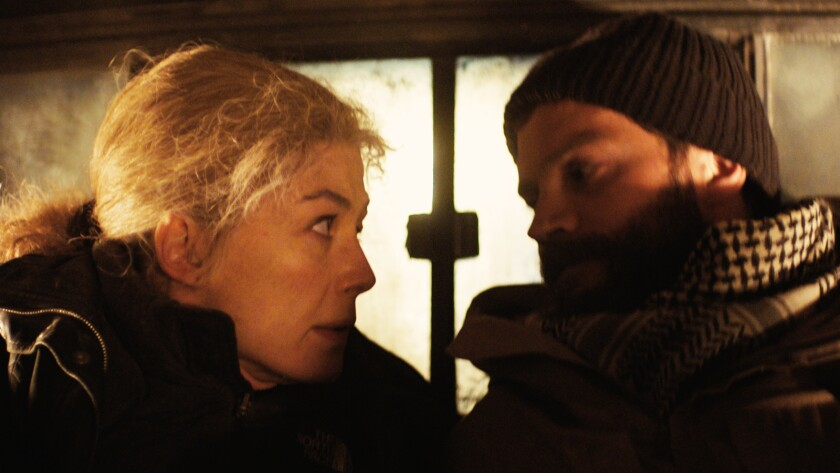 Marie Colvin (Rosamund Pike) and Paul Conroy (Jamie Dornan) fearfully drive through a warzone in A P