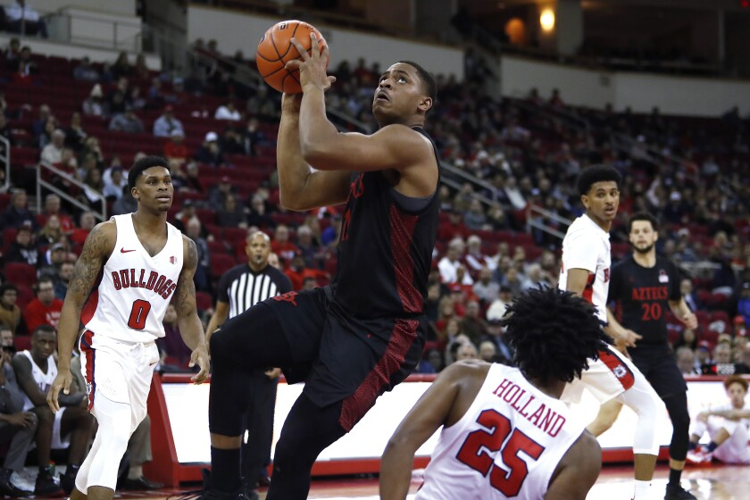 San Diego State's Matt Mitchell drives to the basket between Fresno State's New Williams (0) and Anthony Holland during the first half of Tuesday's college basketball game in Fresno.