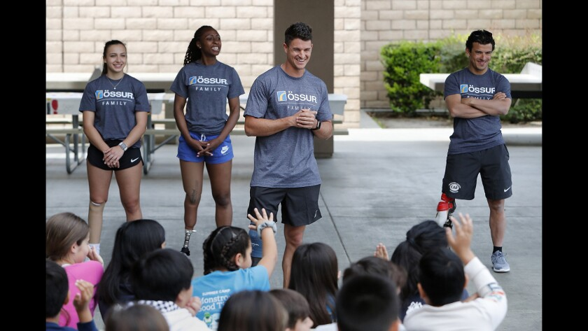 Team USA long jumper Trenten Merrill, center, answers questions from kids at Woodbury Elementary School in Irvine on Thursday, April 11, 2019. Background from left is Team Canada sprinter Marissa Papaconstantinou, Team USA sprinter Femita Ayanbeku and Team USA cyclist and triathlete Mo Lahna. April is National Limb Loss Awareness Month.