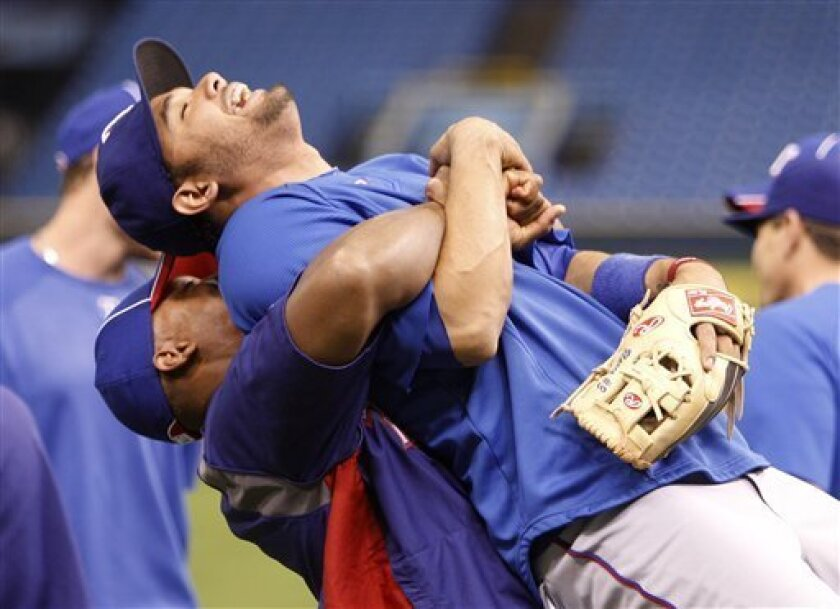 Texas Rangers third baseman Adrian Beltre, left, lifts Andre Blanco into the air during practice for Game 3 of the American League division series, Sunday, Oct. 2, 2011 in St. Petersburg, Fla. The Rangers play the Tampa Bay Rays Monday. (AP Photo/Lynne Sladky)