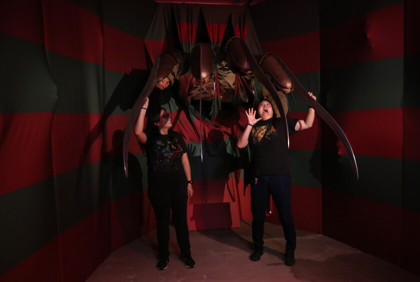 """Cynthia Salazar, left, and Chelsea Salazar pose for a picture at the """"I Like Scary Movies"""" art exhibit in downtown Los Angeles."""