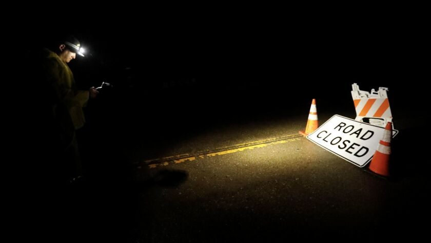 Patrick Braid passes through a closed road to check on residents who sheltered in place in the early morning hours Friday in Montecito.