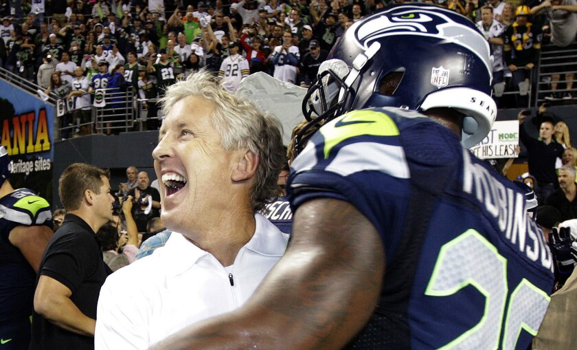 """Seattle Seahawks Coach Pete Carroll celebrates with Michael Robinson after the team's 14-12 win in the infamous """"fail mary"""" game against the Green Bay Packers in 2012."""