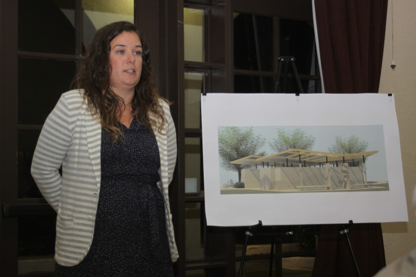 City Project Manager Elizabeth Schroth-Nichols stands next to a rendering of the proposed new Cove Pavilion restroom facility for Scripps Park.