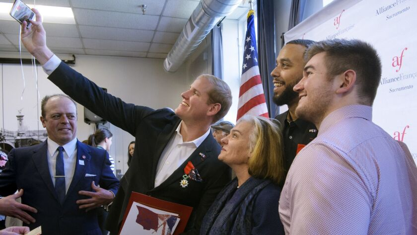 Spencer Stone, left holding the camera, photographs himself and French Conseillere Consulaire Sophie