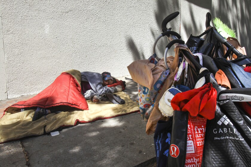 A homeless woman sleep on the sidewalk next to her cart of her belongings on the sidewalk on A Street in San Diego in 2017.
