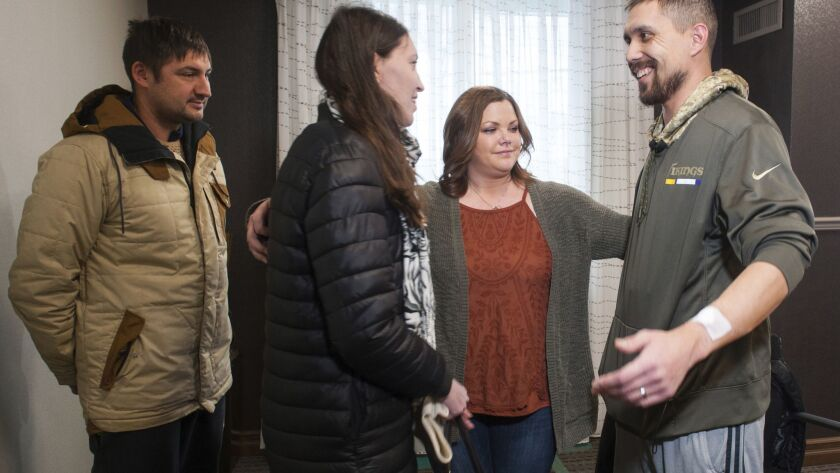 Erin Bond, center, 33, of Apple Valley, Minn., and her husband, John, right, 35, get ready to hug Olga Kemaeva, 34, the widow of Anton Kemaev, as they meet for the first time in 2017, in Pittsburgh. Bond believes he received Kemaev's kidney in a transplant operation.