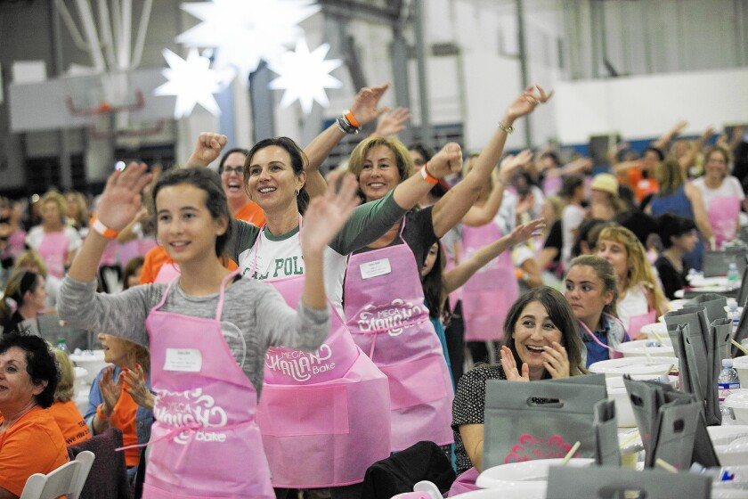 Elisa Costa, left, Mela Evans and hundreds of women dance during the OC Mega Challah Bake at the Misty May-Treanor Sports Center on Thursday.
