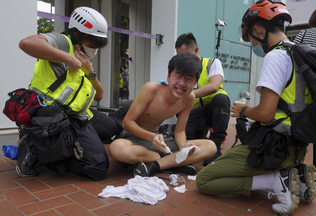 A journalist is treated after being hit by pepper spray during a security law protest in Hong Kong on Wednesday.