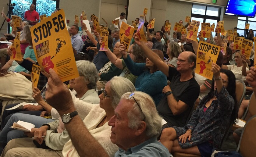 """More than 150 people, many waving """"Stop 5 G"""" posters, attend a city-sponsored workshop Monday on a new city ordinance that will allow 5G antennas to be installed along city rights-of-way."""