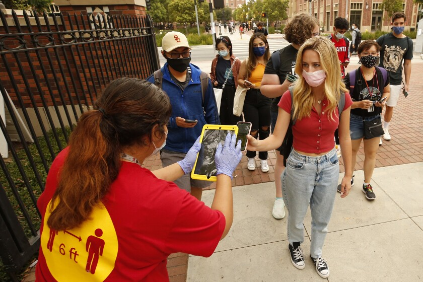 """LOS ANGELES, CA - AUGUST 23: USC CARE Crew Team Ambassador Lesly Plancarte, left, uses the iPad to check the QR code as USC students, faculty and visitors use their phones to display their """"Trojan Check"""" QR code scanned by a QR reader or iPad at various campus gates in order to access the USC campus Monday for the first day of in-person classes. USC and California State University campuses start in-person classes on Monday, serving as a test case for whether vaccine mandates, masking, regular testing and other protocols can minimize spread of the Delta variant even as thousands of students congregate in classes, dorms and social events. USC campus on Monday, Aug. 23, 2021 in Los Angeles, CA. (Al Seib / Los Angeles Times)."""