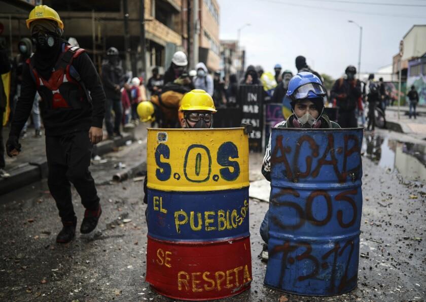 En esta imagen del 9 de junio de 2021, manifestantes antigubernamentales se resguardan detrás de escudos de fabricación casera durante enfrentamientos con la policía en Bogotá. (AP Foto/Iván Valencia, Archivo)