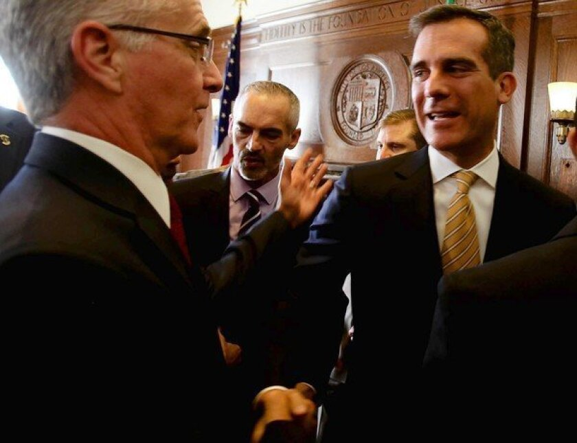 L.A. Mayor Eric Garcetti, right, shakes hands with Councilman Paul Krekorian, a member of the panel that negotiated much of the Department of Water and Power labor agreement.