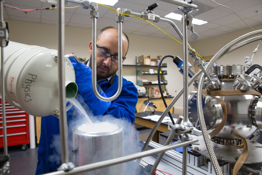 Gerardo Dominguez, an associate professor of physics, works with his Isotopic Characterization Experimental, or ICE, apparatus in his research lab at Cal State San Marcos.