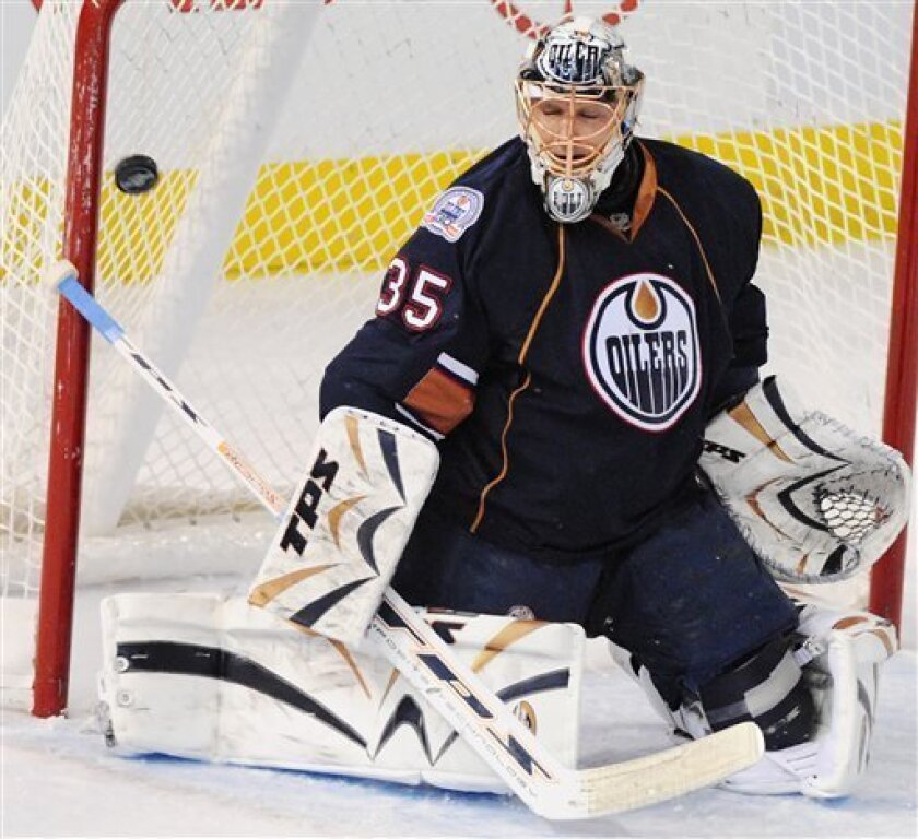 A shot by Vancouver Canucks' Alexandre Burrows, not shown, gets by Edmonton Oilers goalie Dwayne Roloson (35) during the second period in an NHL hockey game in Edmonton, Alberta on Wednesday, Jan. 7, 2009. (AP Photo/The Canadian Press, Jimmy Jeong)