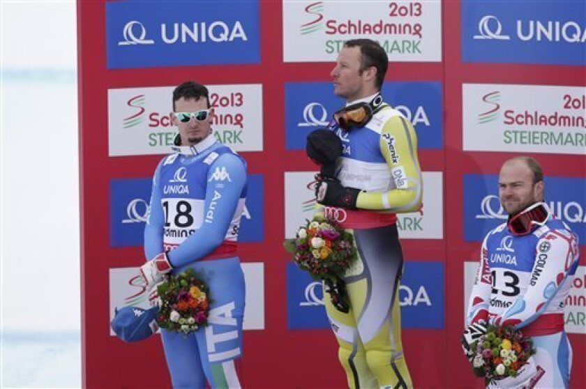 Norway's gold medal winner Aksel LundSvindal is flanked by Italy's silver medal winner DominikParis, left, and France's bronze medalist DavidPoisson during the flower ceremony for the men's downhill at the Alpine skiing world championships in Schladming, Austria, Saturday, Feb. 9, 2013. (AP Photo/Matthias Schrader)