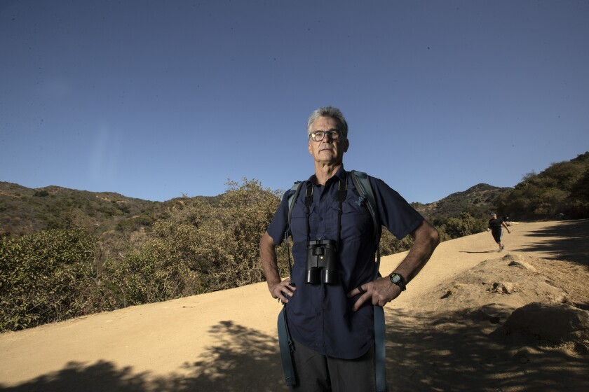 Gerry Hans, binoculars around his neck, stands on the Brush Canyon Trail in Griffith Park.