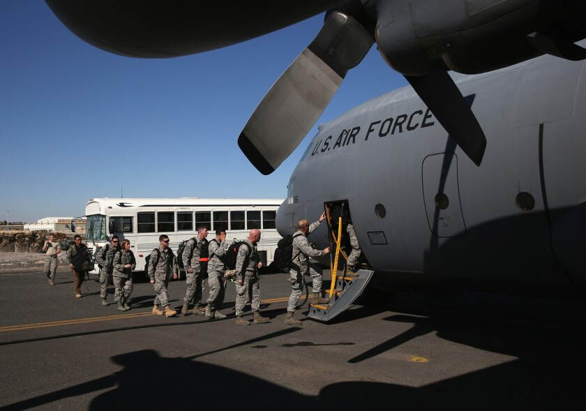 U.S. military personnel board a Texas Air National Guard C-130 cargo plane bound for Iraq on January 10, 2016 from a base in an undisclosed location in the Persian Gulf region.