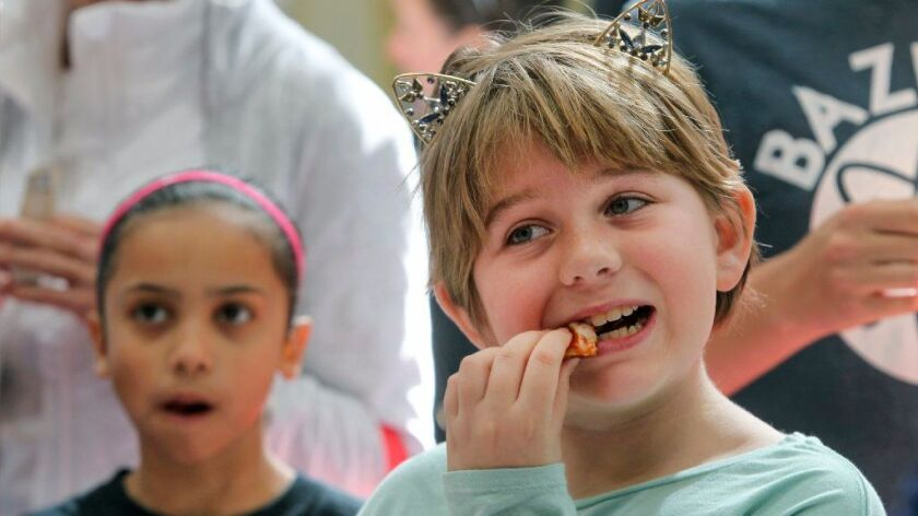 Zoe Cox, 10, samples gluten-free pizza at the Gluten Free & Allergen Friendly Expo in San Diego on Sunday