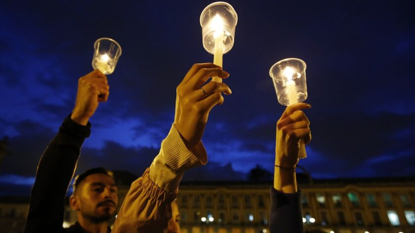 In this July 6 photo, demonstrators in Bogota, Colombia, hold up candles during a candlelight vigil for slain activists who have been killed since the signing of peace accords.