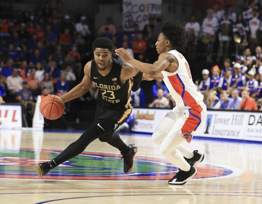Florida State guard M.J. Walker (23) drives to the basket around Florida guard Ques Glover (0) during the first half of an NCAA college basketball game Sunday, Nov. 10, 2019, in Gainesville, Fla. (AP Photo/Matt Stamey)
