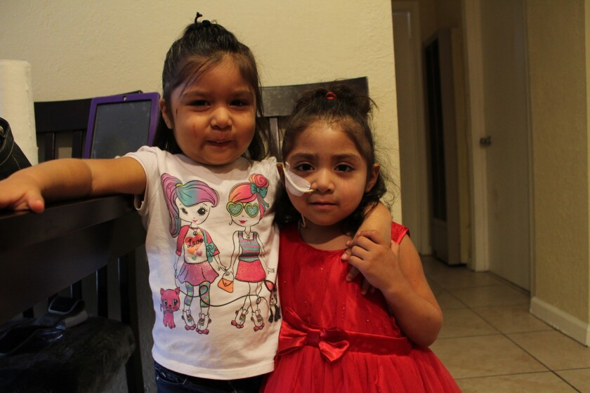 Gigi, con vestido rojo, abraza a su hermanita Yalanda.
