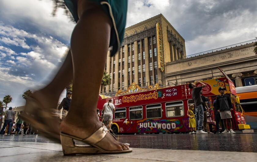 A person walks on a busy Hollywood Boulevard.