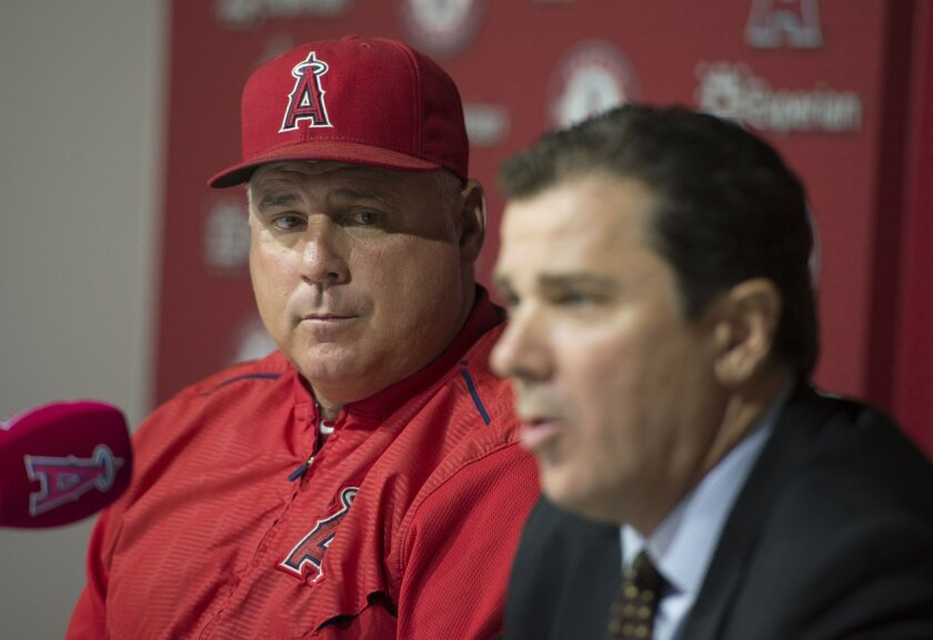 Los Angeles Angels president John Carpino, right, speaks as manager Mike Scioscia listens during a news conference following the Angels' baseball game against the New York Yankees, Wednesday, July 1, 2015, in Anaheim, Calif. The two were on hand to talk about the abrupt resignation of general manag