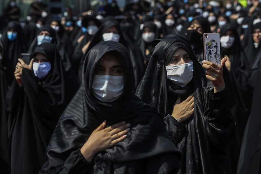 People wearing protective face masks to help prevent spread of the coronavirus mourn during an annual ceremony commemorating Ashoura, the anniversary of the 7th century death of Imam Hussein, a grandson of Prophet Muhammad, and one of Shiite Islam's most beloved saints, who was killed in a battle in Karbala in present-day Iraq, at the Saleh shrine in northern Tehran, Iran, Sunday, Aug. 30, 2020. Authorities allowed limited mourning rituals, urged social distancing and made wearing masks mandatory. (AP Photo/Ebrahim Noroozi)