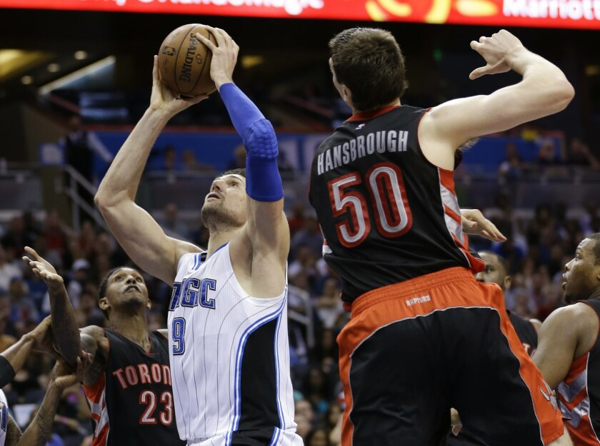 After grabbing an offensive rebound, Orlando Magic's Nikola Vucevic (9) takes a shot between Toronto Raptors' Tyler Hansbrough (50) and Louis Williams (23) during the second half of an NBA basketball game, Friday, April 10, 2015, in Orlando, Fla. Toronto won 101-99. (AP Photo/John Raoux)