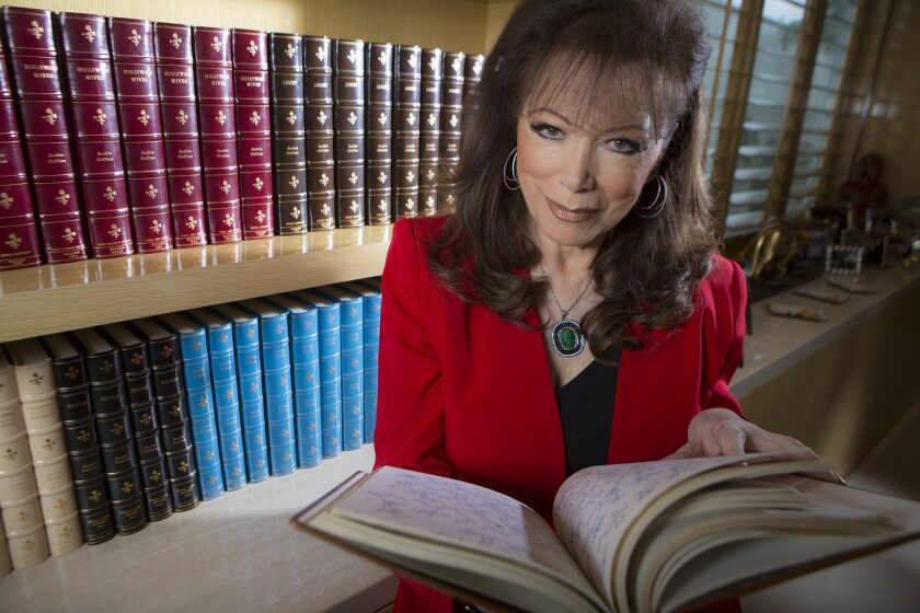 Author Jackie Collins with her leatherbound manuscripts. She died Saturday at 77. She was beloved by readers, who saw the fun in the heightened reality she portrayed.
