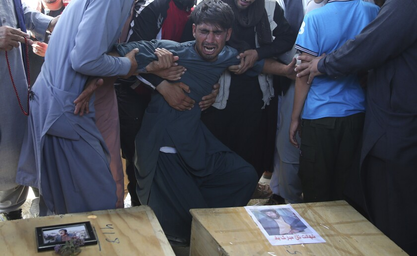 A relative wails near the coffins of victims of the Dubai City wedding hall bombing at a mass funeral in Kabul, Afghanistan, Sunday.