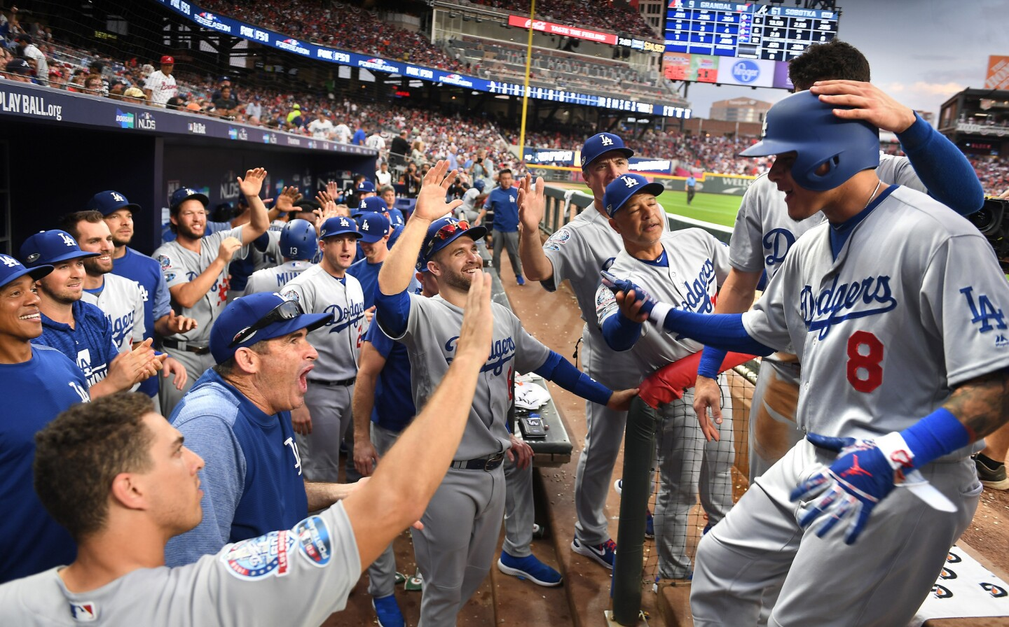 Dodgers shortstop Manny Machado is congratulated by teammates and coaches after hitting a three-run home run in the seventh inning.