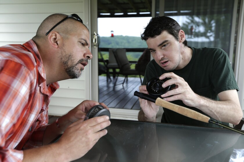 Richard Norris, right, shows friend Andrew Kahle how to load line into a fly fishing rod at Norris' home in Hillsville, Va. Norris, whose face was disfigured by a gunshot, received a face transplant in 2012.