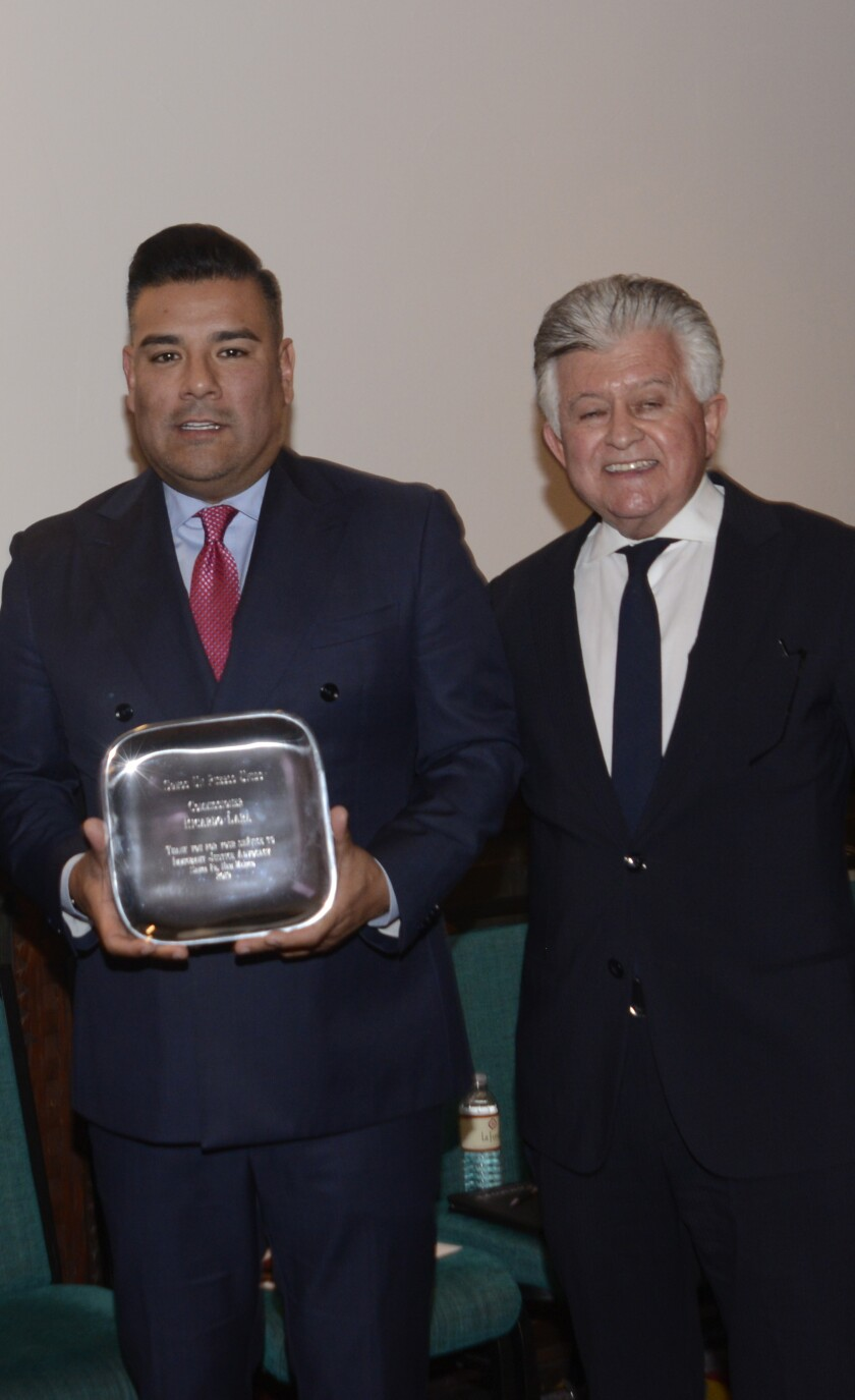 California Insurance Commissioner Ricardo Lara, left, accepts an award from lobbyist Eric Serna in February. Serna's company donated thousands of dollars to Lara.