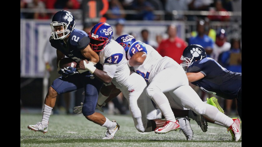 Loyola running back Drake Beasley Jr. is dragged down by Serra defensive end Oluwole Betiku in first half of a game Sept. 25 at Loyola High.