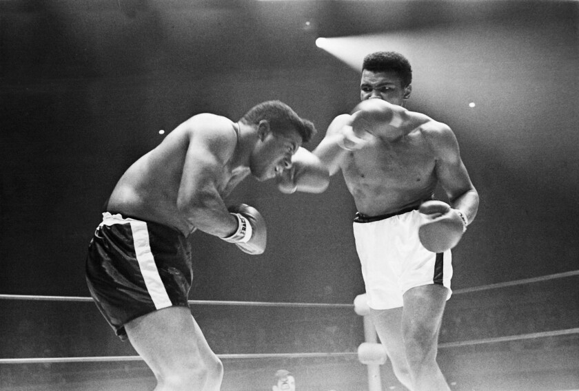 Muhammad Ali takes a swing at Floyd Patterson in a boxing ring in 1965.