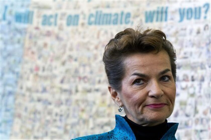 U.N. climate chief Christiana Figueres stands in front of a poster made by Green Peace before the opening of the United Nations Climate Change Conference in Tianjin, China, Monday, Oct. 4, 2010. China, the world's biggest carbon emitter, opened the U.N. conference on climate change aimed at narrowing differences before a major year-end meeting in Mexico. (AP Photo/Alexander F. Yuan)