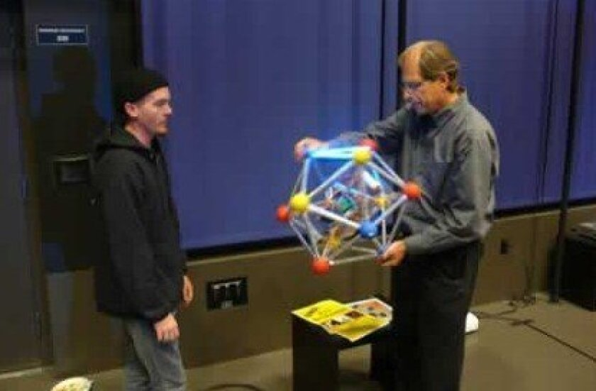 Nick Wolford watches La Jolla resident Fred Raab play with his Techno Icosahedron toy.