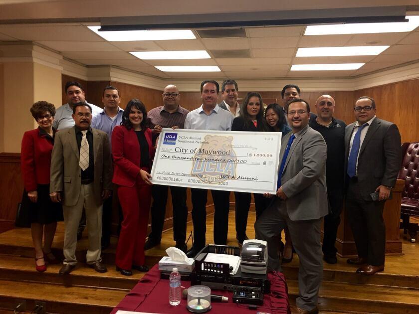 Ricardo Pérez (d) entrega el cheque con Blanca Pacheco (i) a personal y representantes de la ciudad de Maywood, en representación de los Southeast Bruins.