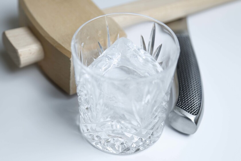 Using a mallet and serrated bread knife, Efren Agustin shapes large blocks of ice into clear frozen cubes that melt slower in a drink and add to the overall presentation of a classic cocktail.