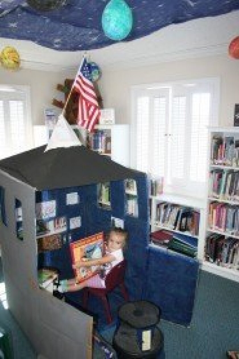 Audri Punaro reads in the spaceship at the RSF Children's Library. Photo by Karen Billing