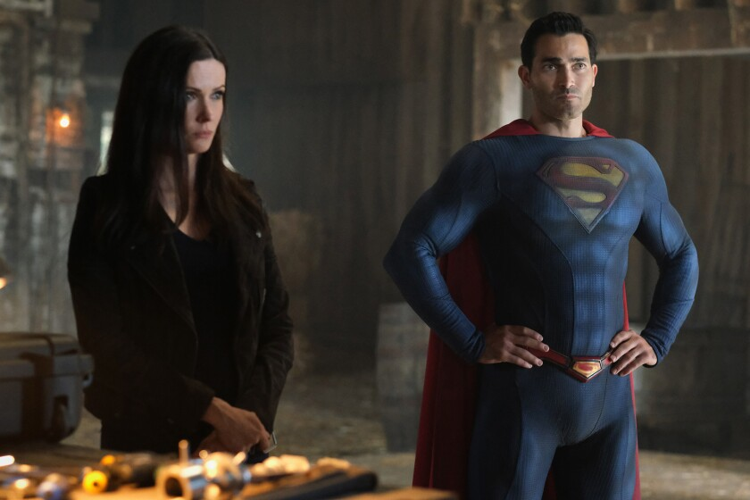 A woman and a man in a blue fitted suit with an S emblem on his chest and a red cape stand while looking forward.