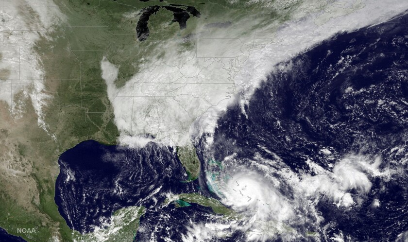 This satellite image taken Friday morning shows Hurricane Joaquin, bottom center, pounding the Bahamas and a deepening low pressure system on the U.S. East Coast.