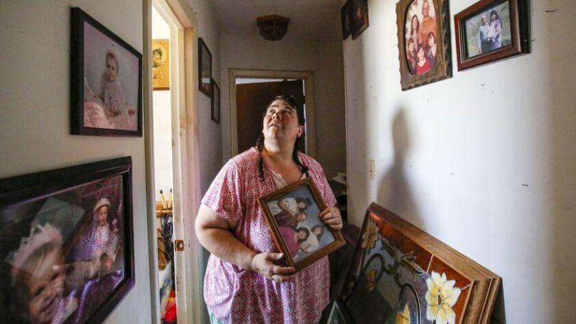 Karen Byrd, de 39 años, recoge los marcos derribados de la pared de su casa en Trona, California. El terremoto dejó gran parte del interior destrozado, pero no hubo daños estructurales importantes en la casa. (Irfan Khan / Los Angeles Times)