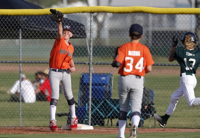 Ocean View Little League No. 2 team's Jack Gollinger, left, secures an out at first base against Cos