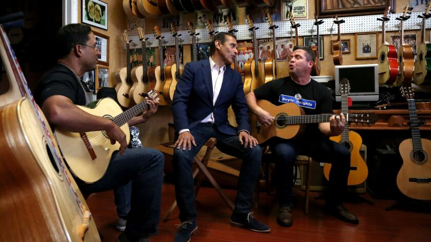 Antonio Villaraigosa, center, sings with Tomas Delgado, left, the owner of Candelas Guitars, and George Magallanes, as he campaigns in the Boyle Heights.