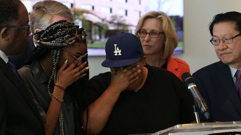 Students Myriah Smiley, 19, and Norma Castillo, 32, break down at the podium during a press conference at the Los Angeles Trade Technical College.