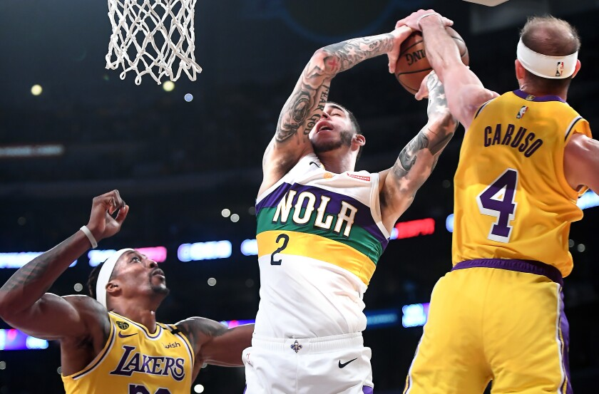 Lakers guard Alex Caruso blocks a shot by Pelicans guard Lonzo Ball during the fourth quarter of a game Feb. 25, 2020, at Staples Center.